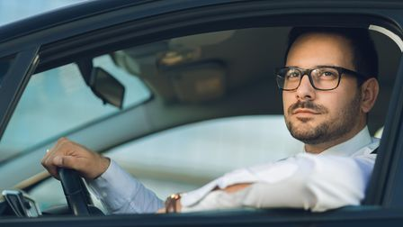 Young businessman going on a business trip by car