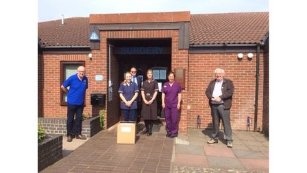Ian Davies handing over the first consignment to staff at Bridge Road Surgery with the Presidents of