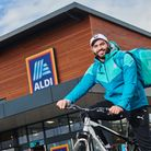 A Deliveroo cyclist delivering groceries from Aldi