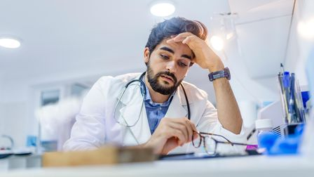 Overworked doctor in his office. Tired male scientist trying to focus, rubbing his forehead with fin