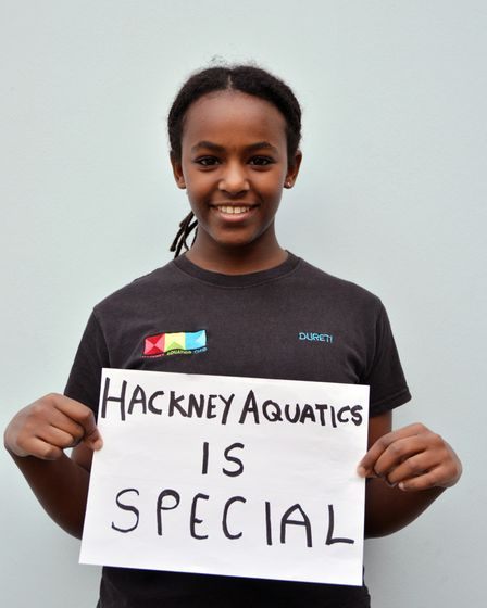 """Hackney swimmer holds up sign saying: """"Hackney Aquatics is special."""""""