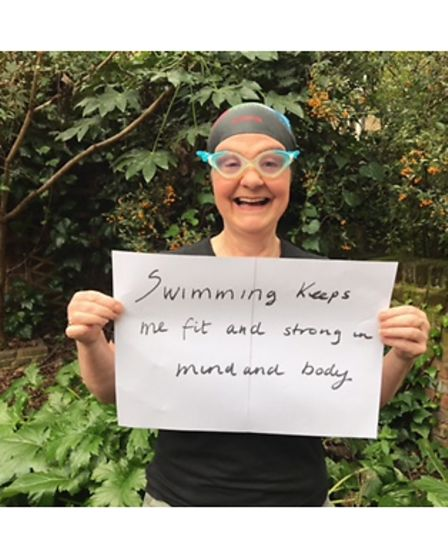 Woman in swimming gear holds up sign saying why she enjoys swimming.