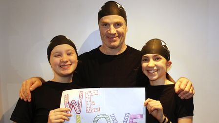 """A family of swimmers holds up a sing which reads: """"We love swimming."""""""