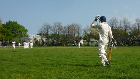 A wicket has just fallen in a cricket match, and the new Batsman heads out onto the field to face up