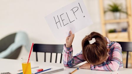 Small girl feeling desperate and holding HELP sing while homeschooling during virus epidemic.