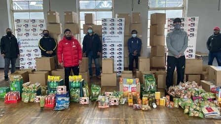Capital Kids Cricket staff and volunteers with food items