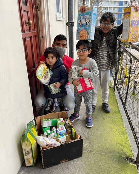 Children with a food box delivered by the Capital Kids Cricket project.
