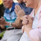 Elderly woman clasping hands together during an activity at Osborne Care Homes