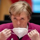Angela Merkel removes her face mask at the start of a cabinet meeting at the Chancellery in Berlin