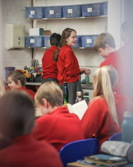 Year six pupils queue up to wash their hands before the start of the school day at St Thomas More Catholic Primary School...