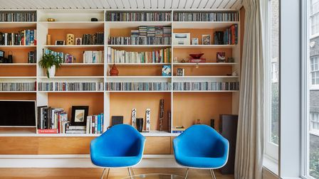 A well designed living area with two blue chairs and built-in shelving.