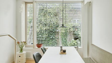 White dining area with exterior venetian blinds, built in bench seating and an Eames designed mid-century table