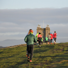 Park runners running up a hill at Lyme Park