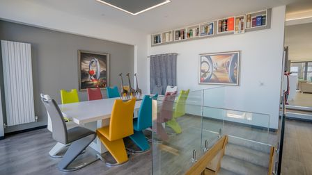 Modern dining room in the house for sale in Hillside Road Portishead with colourful chairs around a white plastic dining...