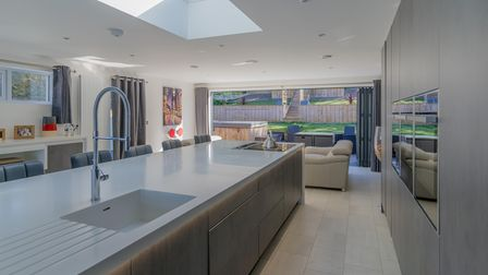 white kitchen with island including a sink, multiple ovens inset into the right-hand wall and living area behind in the...