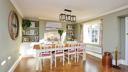 The large dining room of the house in High Street Claverham for sale which has parquet flooring, sage-green walls and a...