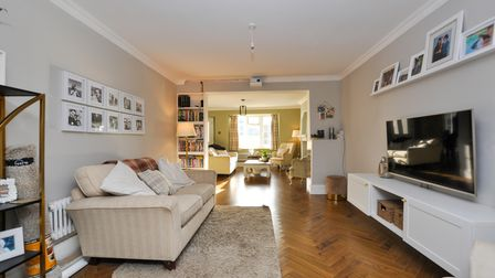 Sitting room in the house in High Street Claverham with parquet floor, beige sofa in front of a TV on the wall with white...
