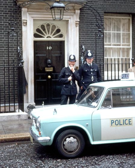 London, England, UK, 1976. Streetscene: two police officers with their police car in front of Downin