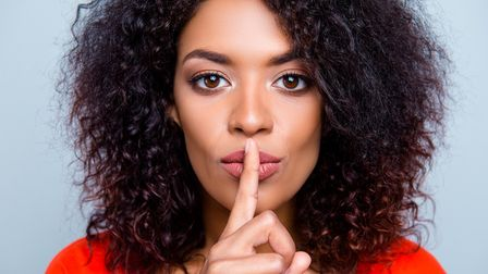 Shh! Closeup portrait of mysterious charming woman with modern hairdo asking for keeping silence hol