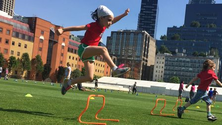 Child jumping over a hurdle on a sunny sports day event