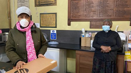 A local resident receives a laptop from Reverend Rosemia Brown, St James Church in Clapton.