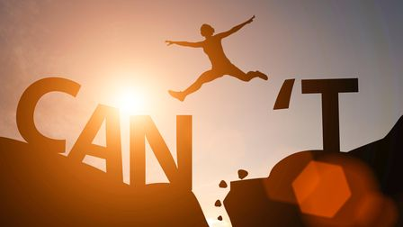 Silhouette man jump between can't wording and can wording on mountain. Mindset for career growth bus