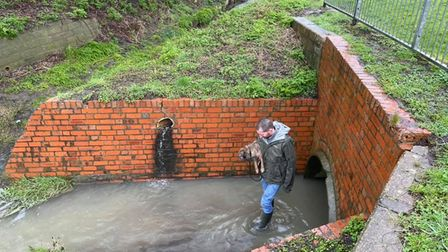 Tim Wylie, a member of the St Neots Drain Watch group walking through the river.