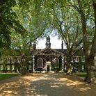 A wide-angle shot of the Geffrye Museum almshouses in the sunshine. The view is down the central pat