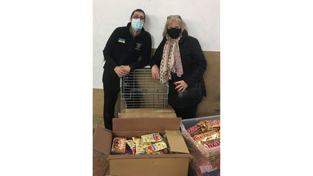 Shop worker and charity worker with food appeal donations