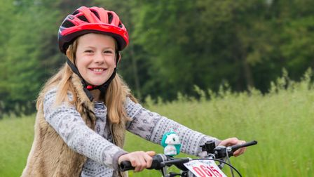 Girl on a bicycle taking part in the Helen Rollason Cancer Charity bike ride in a previous year