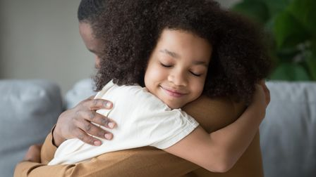 Cute funny mixed race child daughter embracing black father holding tight feeling love connection af