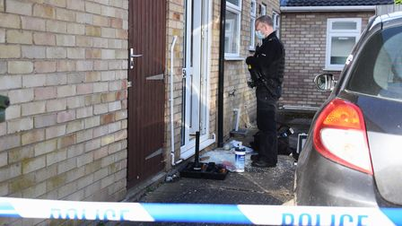 A police officer at the flats in Clover Road, Sprowston, by a damaged door after an aggravated burgl