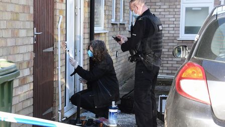 Police and forensics officers at the flats in Clover Road, Sprowston, by a damaged door after an agg