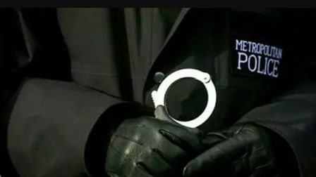 Police officer holding hand cuffs.
