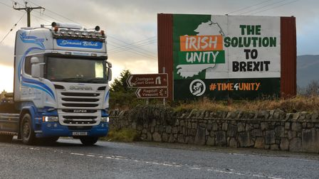 """A lorry passes by a billboard calling for """"Irish Unity - the solution to Brexit"""" on theborder between Republic of Ireland..."""