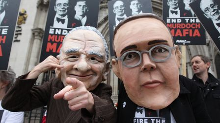 Protesters from the campaign group 'Avaaz' demonstrate outside the High Court with large James and Rupert Murdoch masks