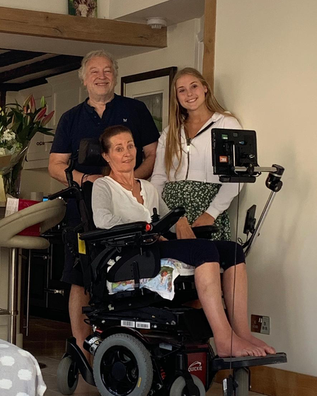 A family photo of a dad, teenage daughter and mother in a wheelchair taken inside their family home.
