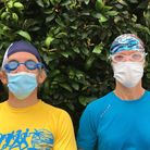 Two men stand next to each other wearing swimming caps, goggles and face masks.