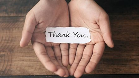 Two hands hold a piece of paper that says thank you