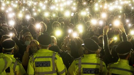 People in the crowd turn on their phone torches as they gather in Clapham Common, London, after the