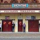 Photograph showing the outside of an Edwardian seaside theatre with four men stood outside