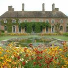 Lively flowerbeds frame this view of Strode House and the lily pond at Barrington Court in Somerset.