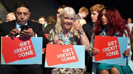 """Delegates hold """"Get Brexit Done"""" posters during the first day of Conservative Party Conference 2019."""