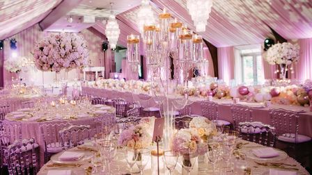 A pink and white setting in a marquee, with chandeliers, balloons and lots of pink