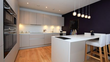 Kitchen with grey units and white worktops, double set of black oven and appliances and downlighters over a breakfast bar