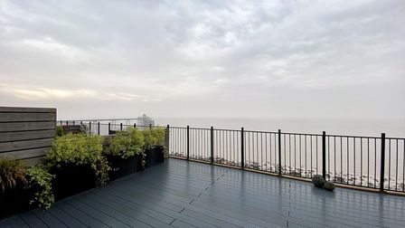 Grey composite decked terrace with black railings in front, planters with shrubs on the left and sea and pier views beyond.