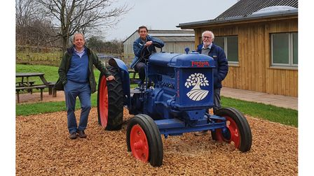 Management team at farm attraction pose for photograph with tractor