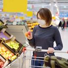 Young woman wearing disposable medical mask shopping in supermarket during coronavirus pneumonia out