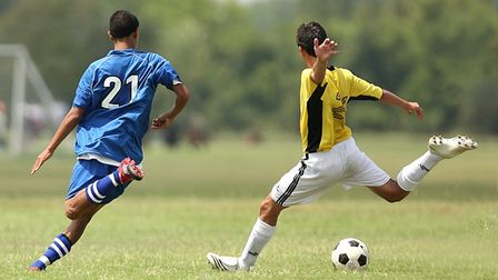 Two youth footballers in action on the pitch