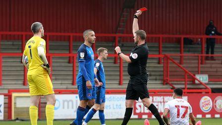 Rod McDonald of Carlisle United is shown a red card after fouling Elliott List
